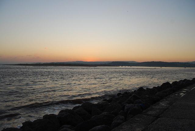 Photograph of ocean and riprap at dusk